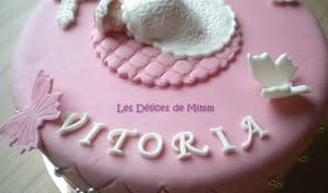 Un gâteau de baptême rose avec des papillons