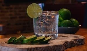 Verre de cocktail gin tonic et rondelles de citron vert