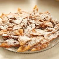 Assiettes de beignets (bugnes) saupoudrés de sucre glace