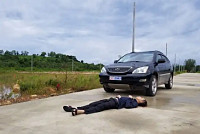 A man sleeps in front of a car...