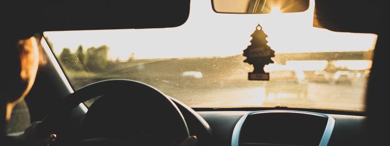 Auto fährt auf Autobahn in Richtung Sonne während ein Duftbaum im Fenster hängt