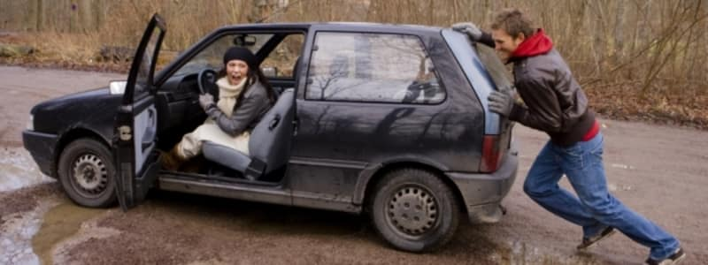 Mand forsøger at skubbe bil i gang i vådt vejr