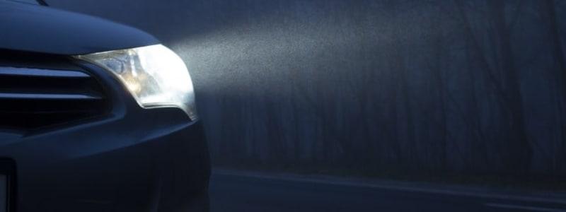En bils forlygte lyder mørk vej op