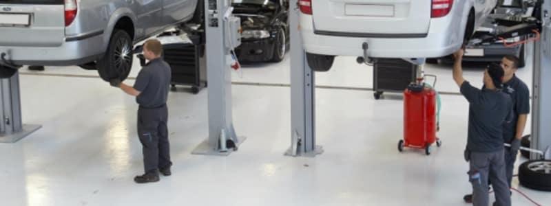 Værksted med mekanikere, der tjekker biler