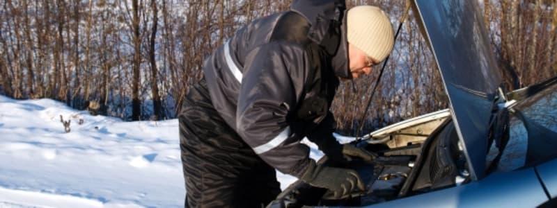 Mand tjekker motor på bil i sneen
