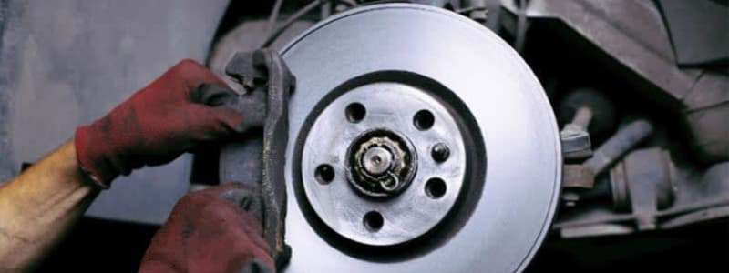 En mekaniker pudser bremseskiven