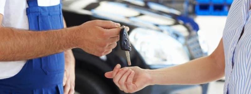 Mekaniker giver bilnøgler til kunde