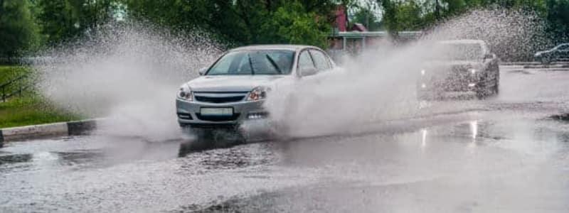 Oversvømmet vej, hvor bil kører igennem