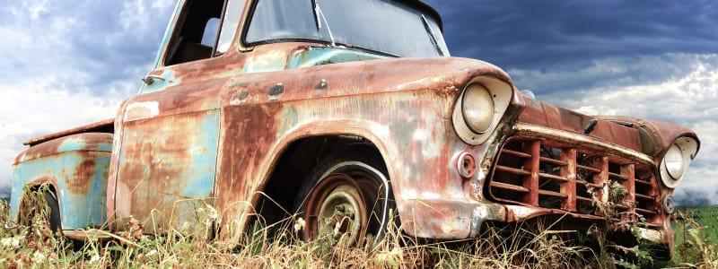 Sommerdag med en rusten bil på en græsmark