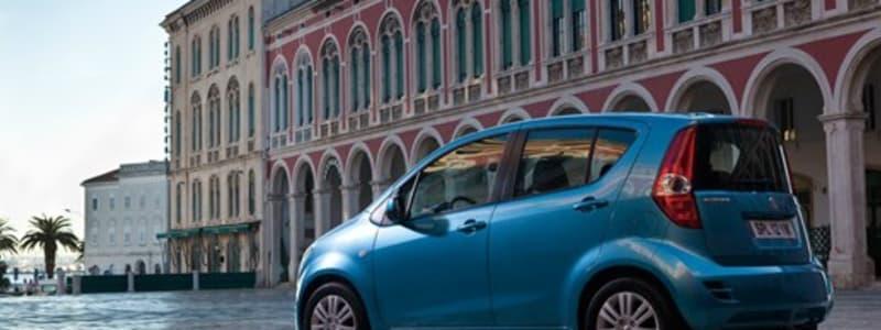 Åben plads i byen med blå bil