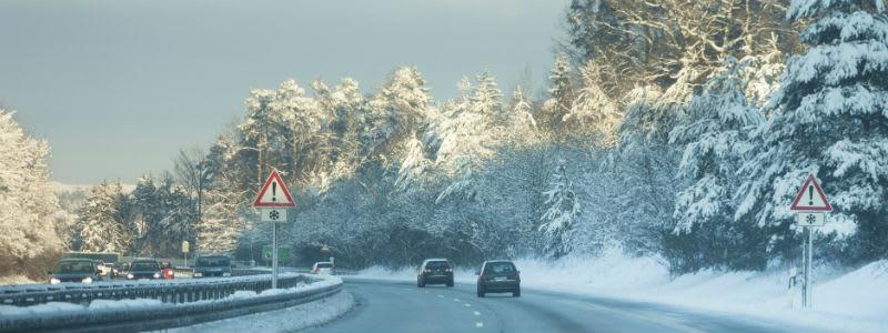 Bil på vej med sne og et skilt med advarsel om glatføre