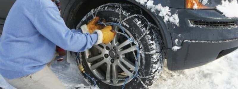 Bil i sneen og mand der sætter snekæder på