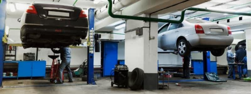 Mekaniker arbejder på to biler på værksted