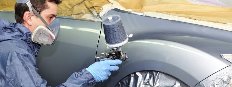 Homme effectuant des retouches de peinture sur la carrosserie d'une voiture