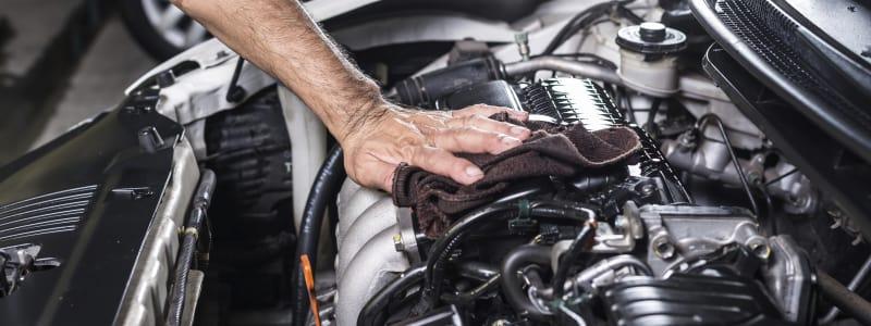 Homme nettoyant un moteur de voiture