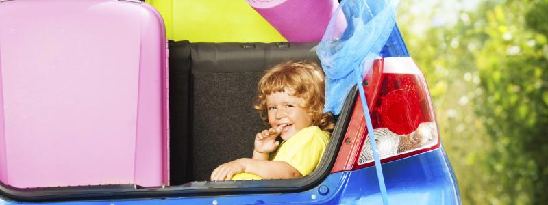 Valises et enfant dans le coffre d'une voiture avant le départ en vacances