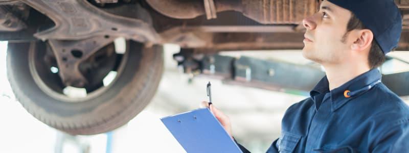 Mécanicien inspectant le châssis d'une voiture
