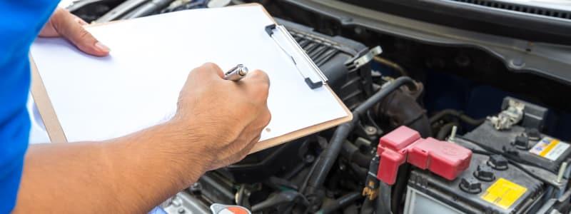 Mécanicien vérifiant le moteur d'une voiture