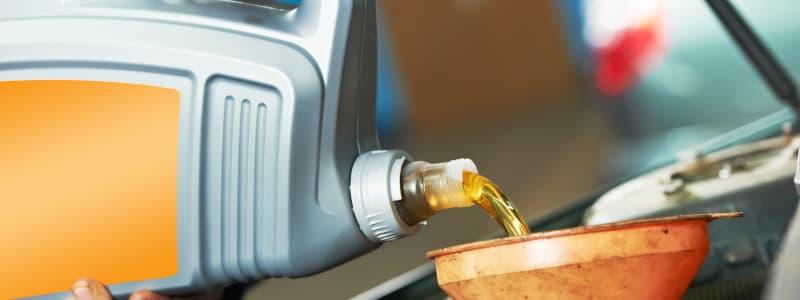 Mécanicien mettant à niveau le liquide du moteur