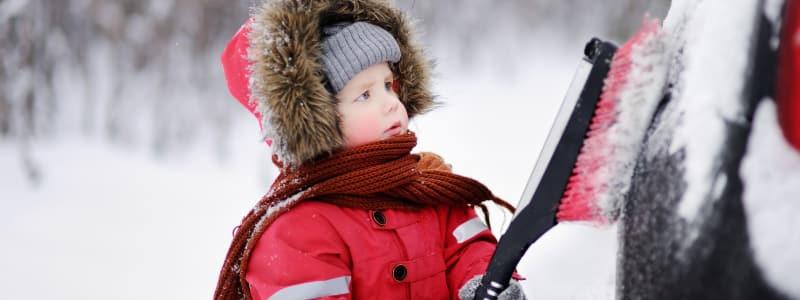 Enfant aidant à déneiger une voiture