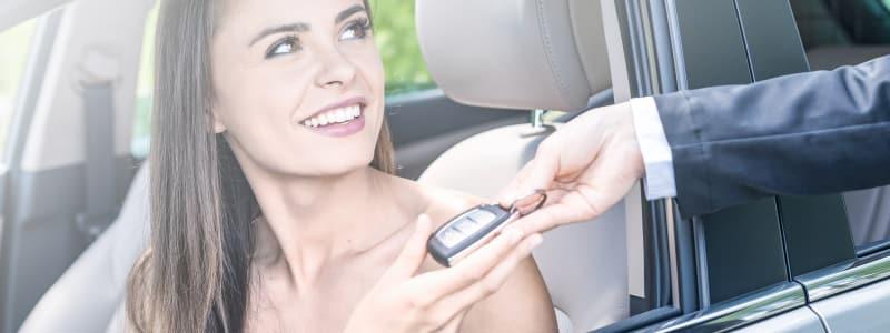 Jeune femme prenant les clés de sa nouvelle voiture