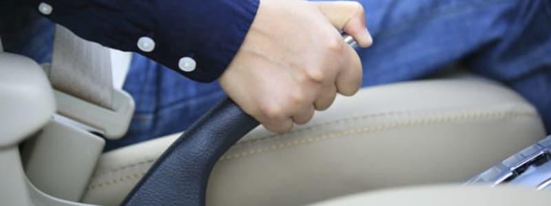 Conducteur activant le frein à main de sa voiture