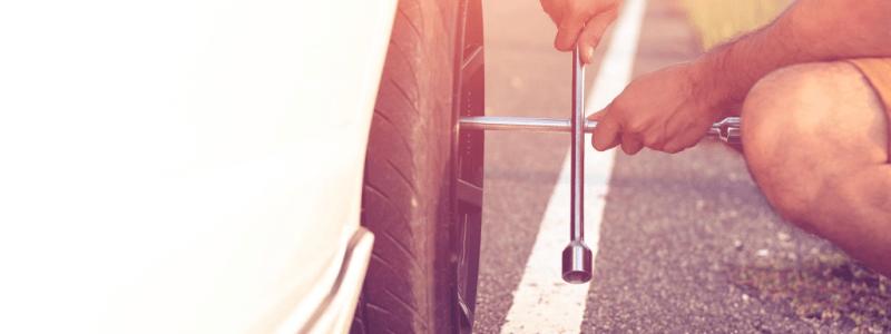Homme changeant un pneu à l'aide d'une clé en croix