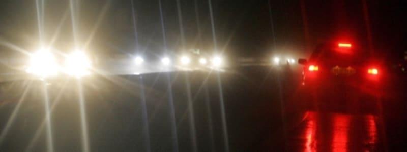 Bilar med felinställda strålkastare på kvällen