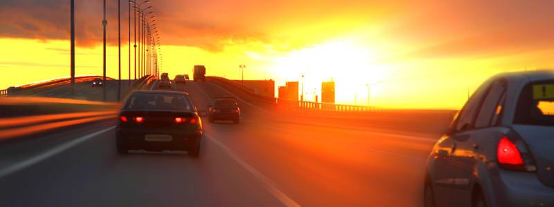 Solnedgång bländar bilar på en väg