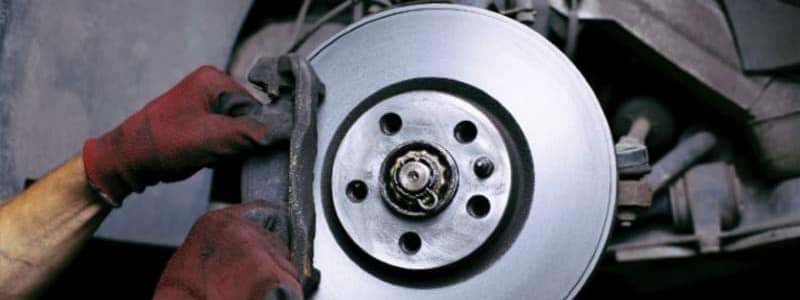 En mekaniker arbetar med bromsar