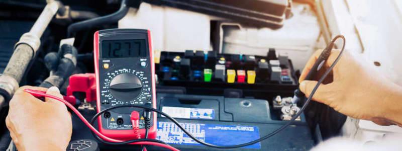 Mekaniker mäter spänning i bilbatteri på Opel