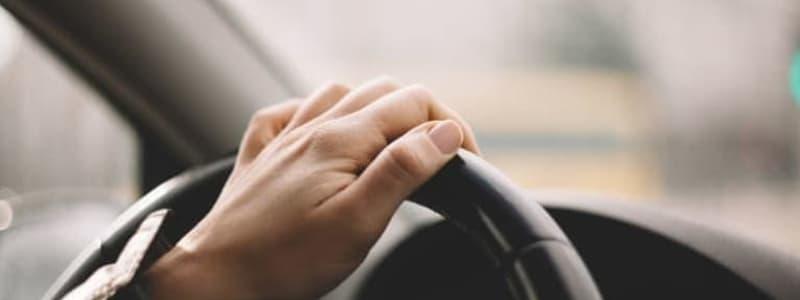 Bilägare med handen på ratten i en Mazda