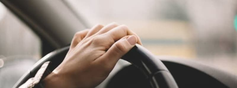 Bilägare med handen på ratten i en Chevrolet