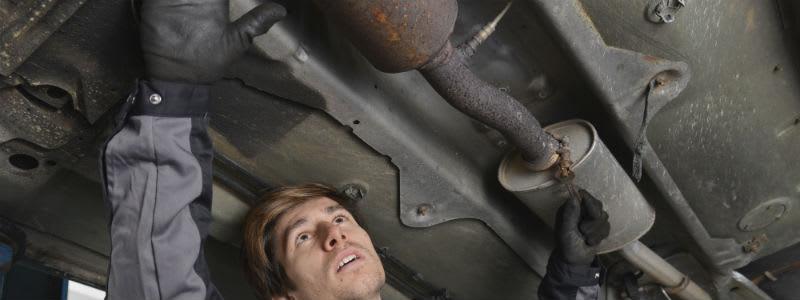 Mekaniker undersöker avgassystem