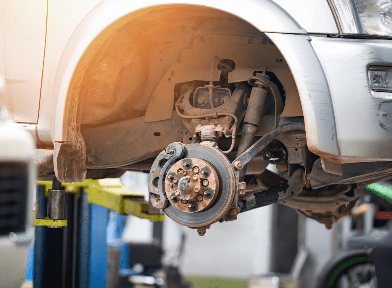Aufgebocktes Auto ohne Reifen um Bremsschlauch zu überprüfen