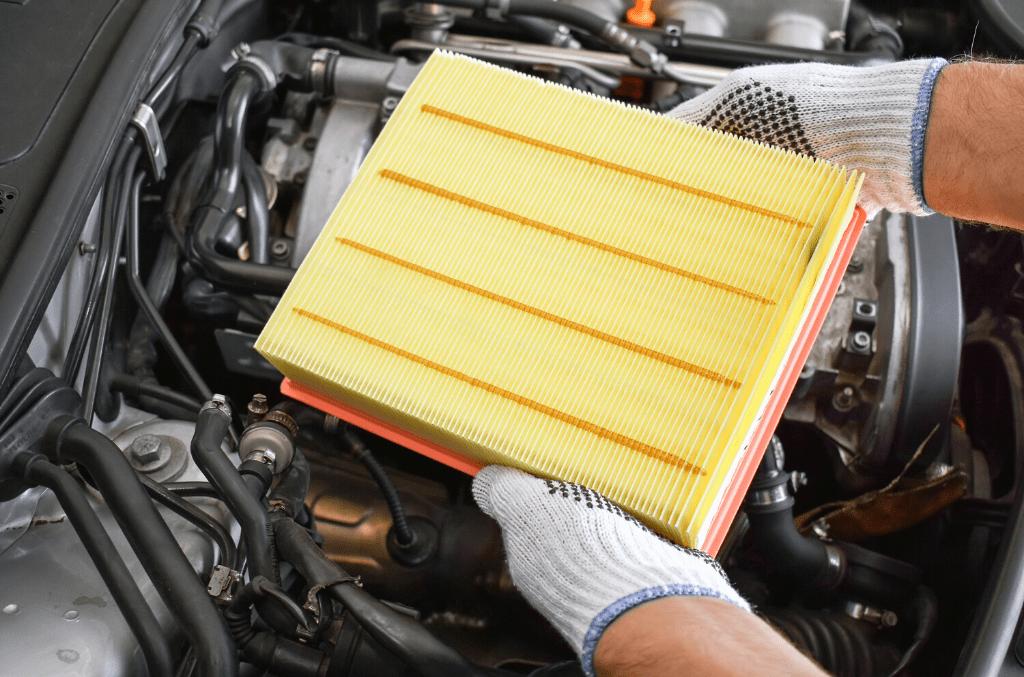Hände die einen gelben Luftfilter im Auto wechseln