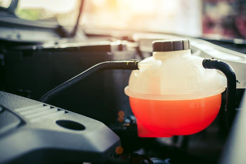 Behälter mit orangefarbener Kühlflüssigkeit unter der Motorhaube