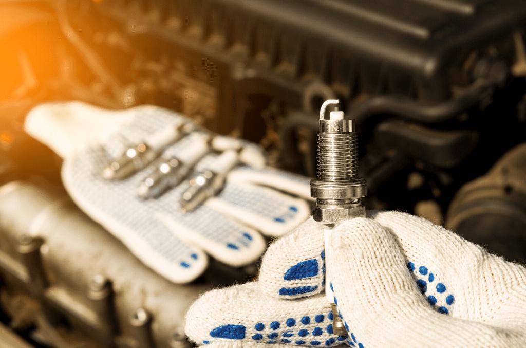 mécanicien tenant une bougie d'allumage automobile