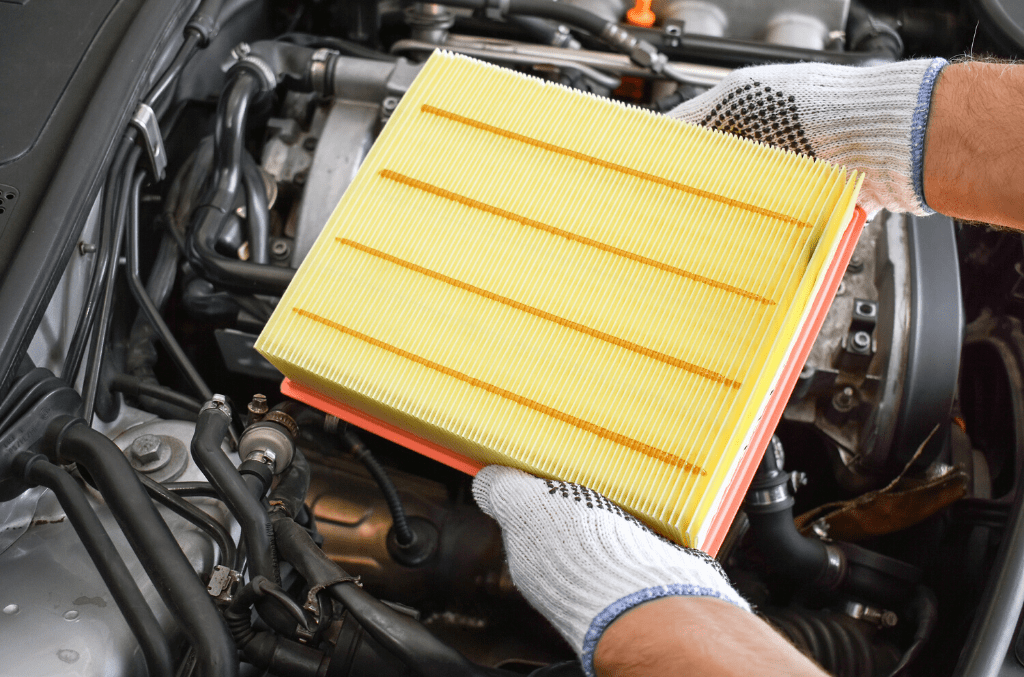 mécanicien tenant un filtre à air automobile