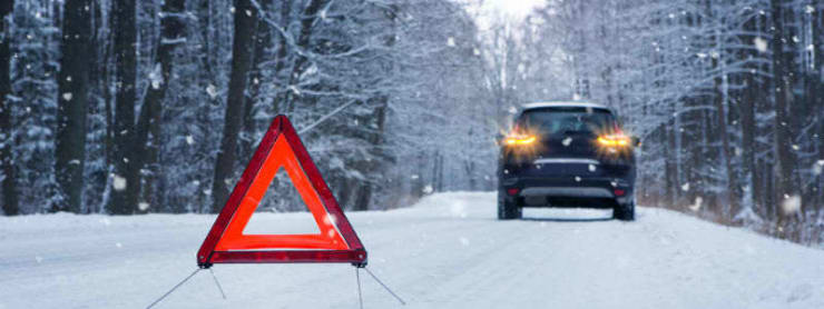 Advarselstrekant på sneklædt vej