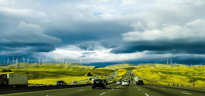 Trafikerad väg på öppet landskap med vindkraftverk