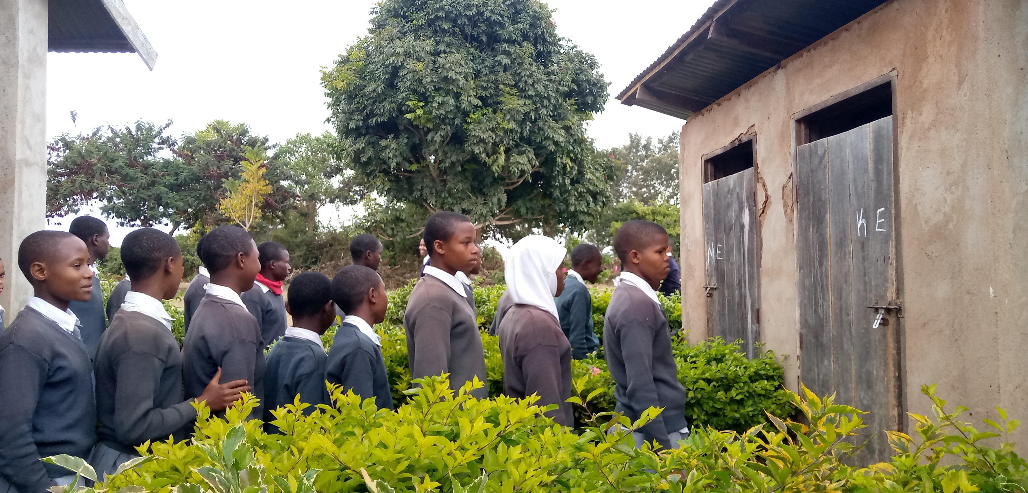 6.31 - Project 2021 - Tsaayo Secondary bathrooms-Students line up to enter bathrooms they share with teachers 06.jpg