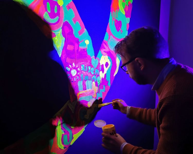 Painting our logo fluorescent - office party