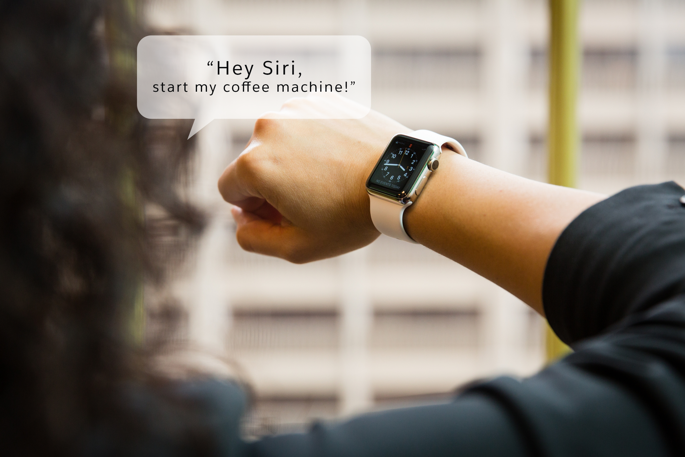 "Photograph of a person speaking to a smart watch. The speech bubble says, ""Hey Siri, start my coffee machine!"""