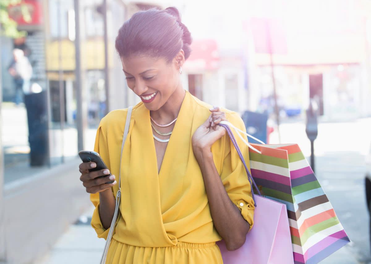 Photographie d'une femme qui sourit dans la rue, en ville. Elle regarde son téléphone et porte deux sacs.