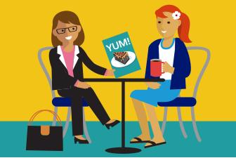 Frau in Geschäftskleidung hält eine Speisekarte mit dem Foto eines Stücks Schokoladentorte der Hand, ihre Freundin sitzt ihr in Rock und Blazer gegenüber