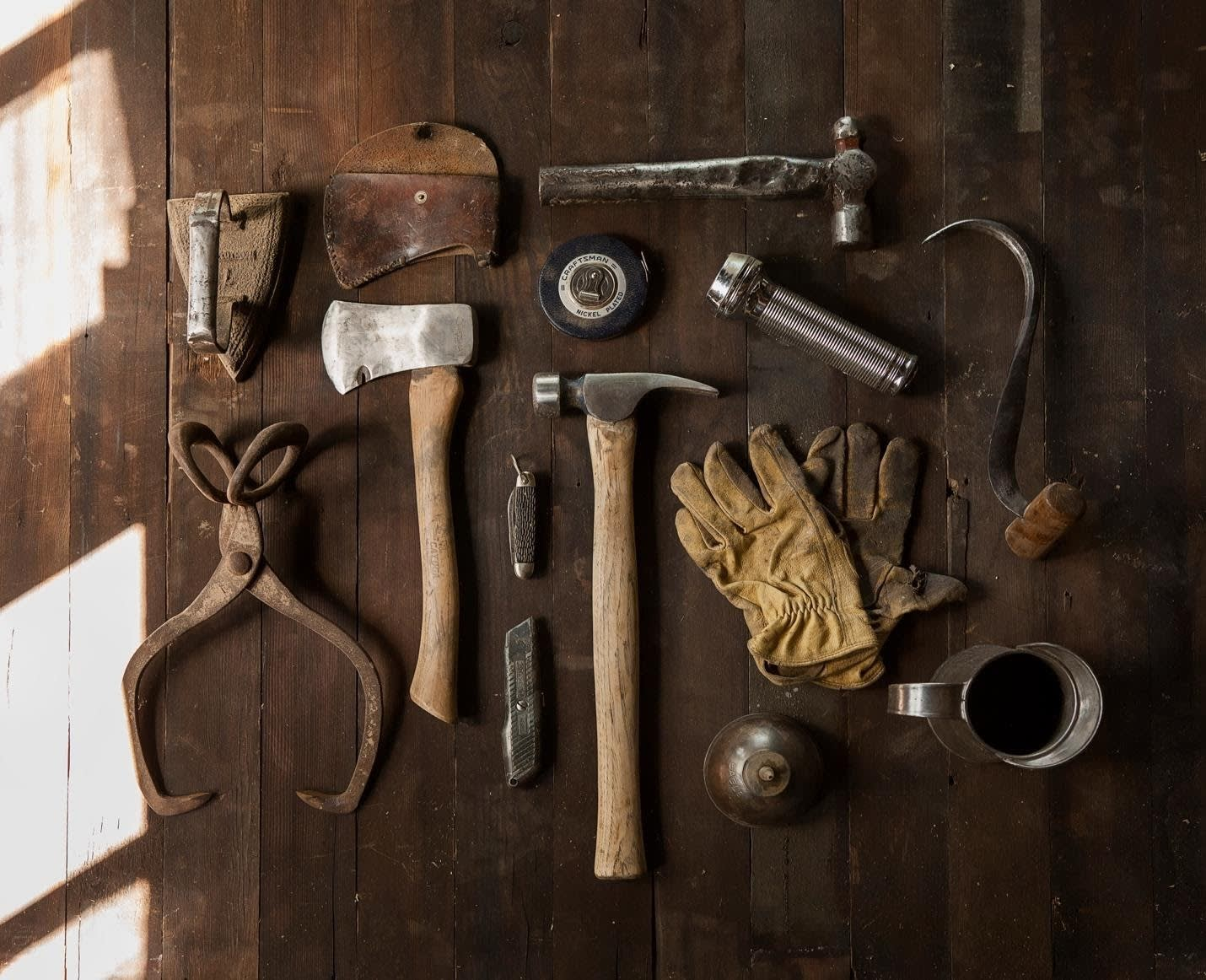 a table with tools on them, including a hammer, mallet, gloves, iron, and more