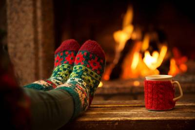 分厚い靴下をはいた人が、ホリデー時期に温かい飲み物を飲みながら暖炉の前でくつろいでいる。