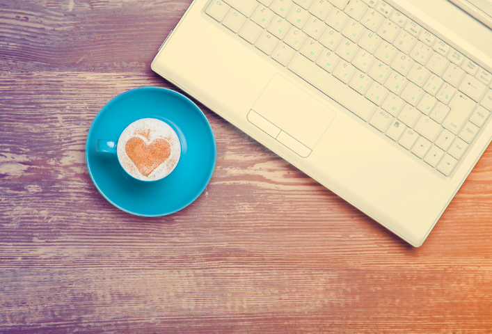 Image of a coffee cup in a saucer near a laptop, delicious coffee with cream and cinnamon sprinkled in the shape of a heart.