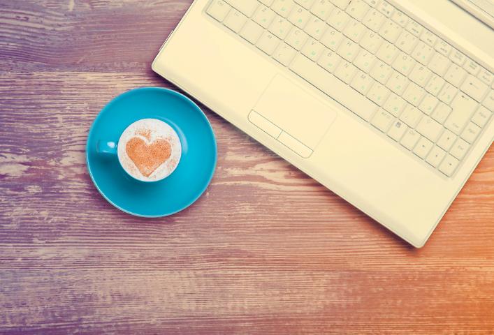 ラップトップのそばに置かれたコーヒーカップとソーサー、クリームにシナモンでハート型が描かれたおいしいコーヒーの画像。